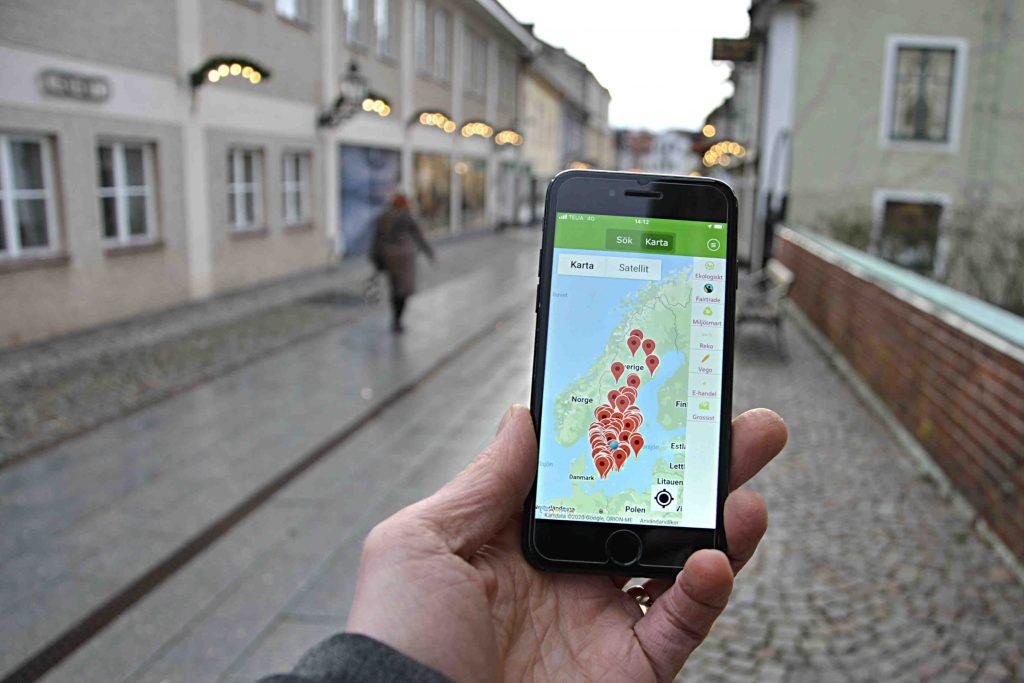 Ekoappen underlättar miljökloak val. Bild på mobil med appen Ekoappen och Vadstenagata i bakgrunden.