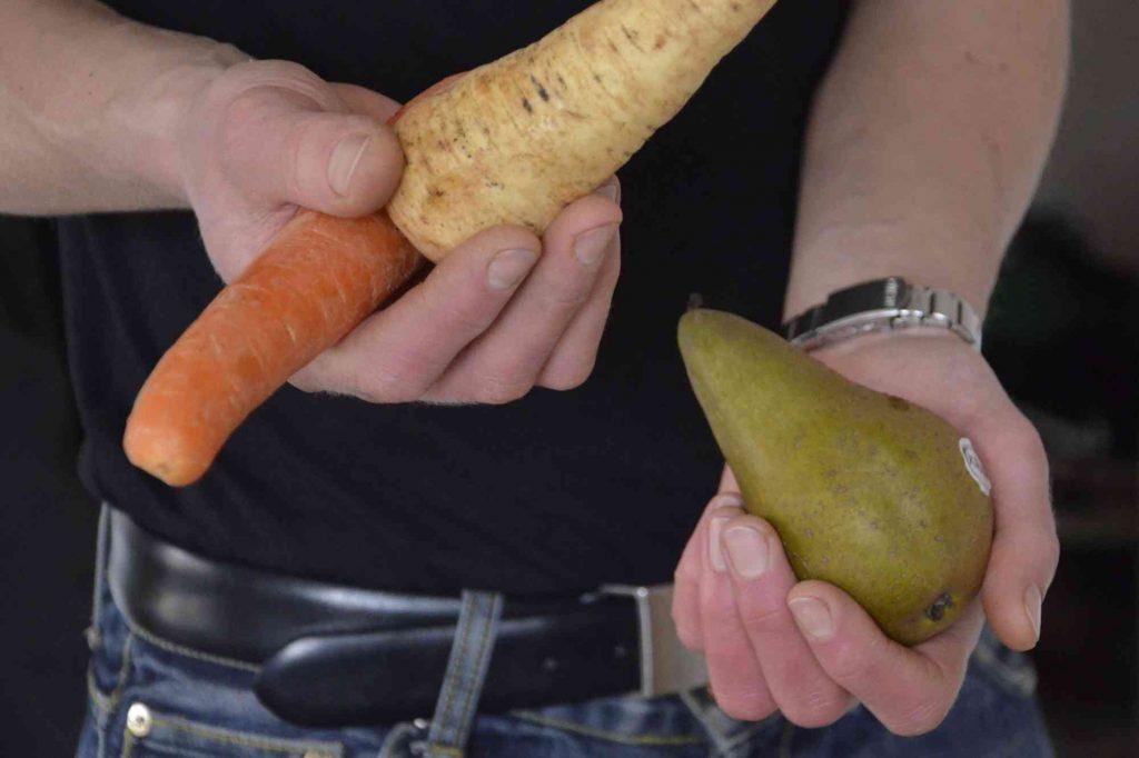 Våga improvisera i köket. Bild på händer som håller rotsaker och en frukt.