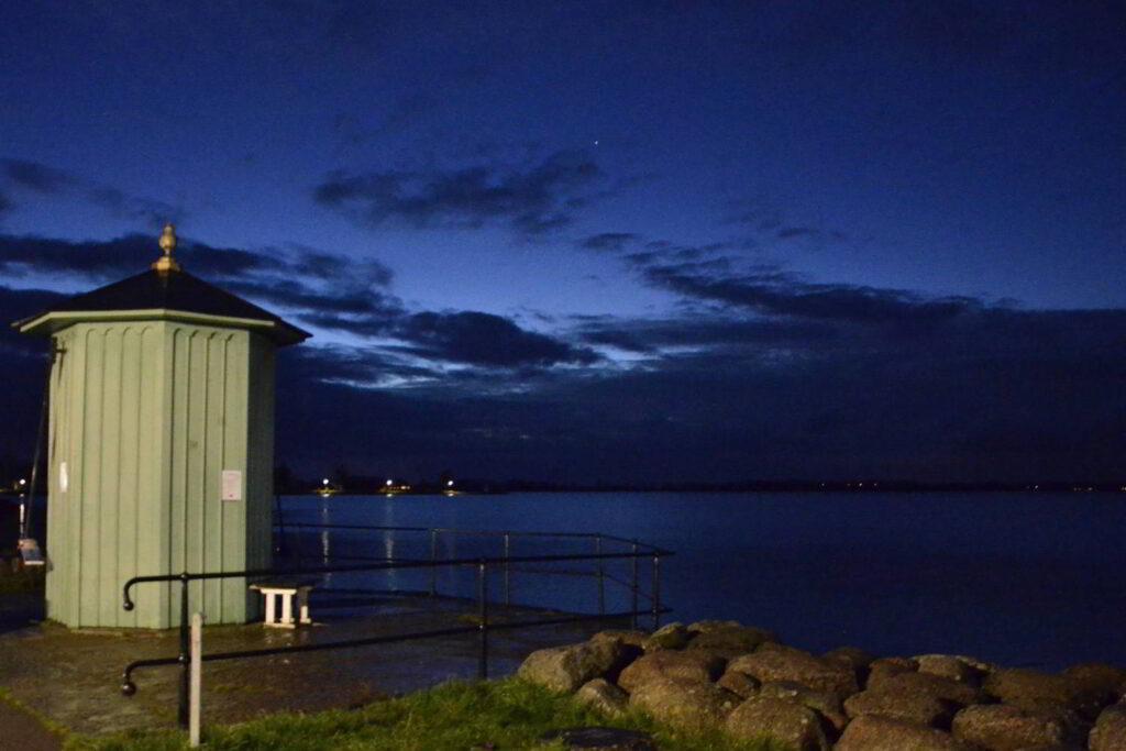 Vättern och klimatförändringarna. Skymningsbild på Pumphuset i Vadstena, vid Vätterns strand.