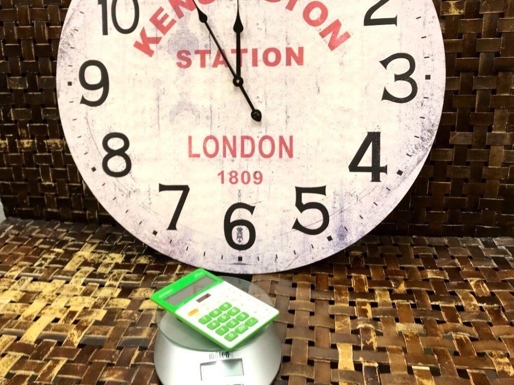 Koldioxidbudget. Bild på miniräknare som ligger på en våg och en stor klocka i bakgrunden som visar fem i tolv.