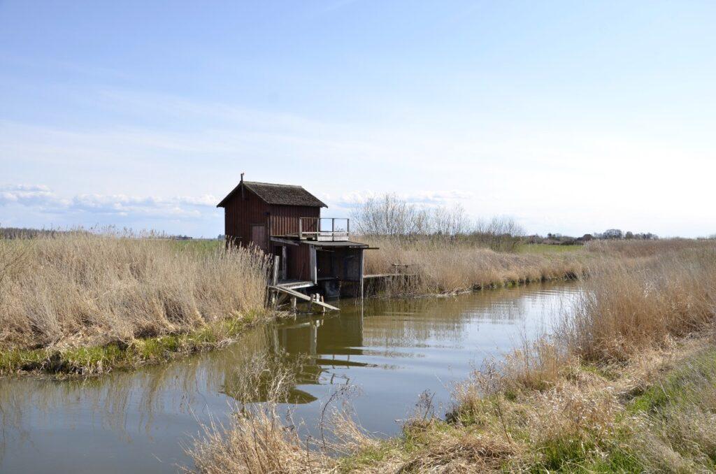 Att upptäcka närheten. Bild på mindre byggnad vid en liten å med fält i bakgrunden.