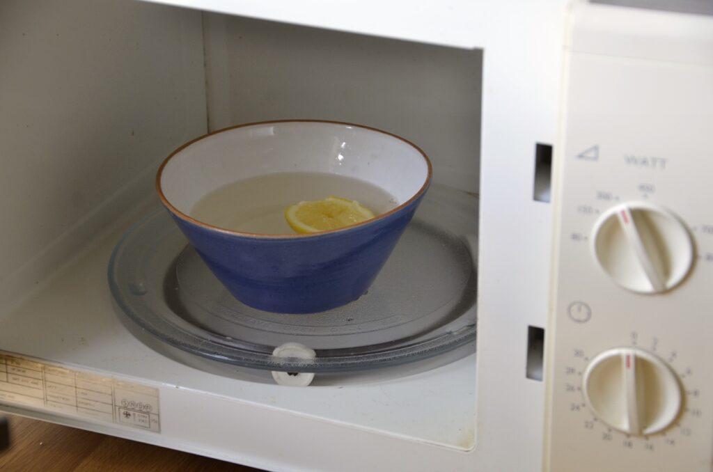 Rengöra med citron. Bild på citronhalva i tallrik med vatten inne i en mikrovågsugn.